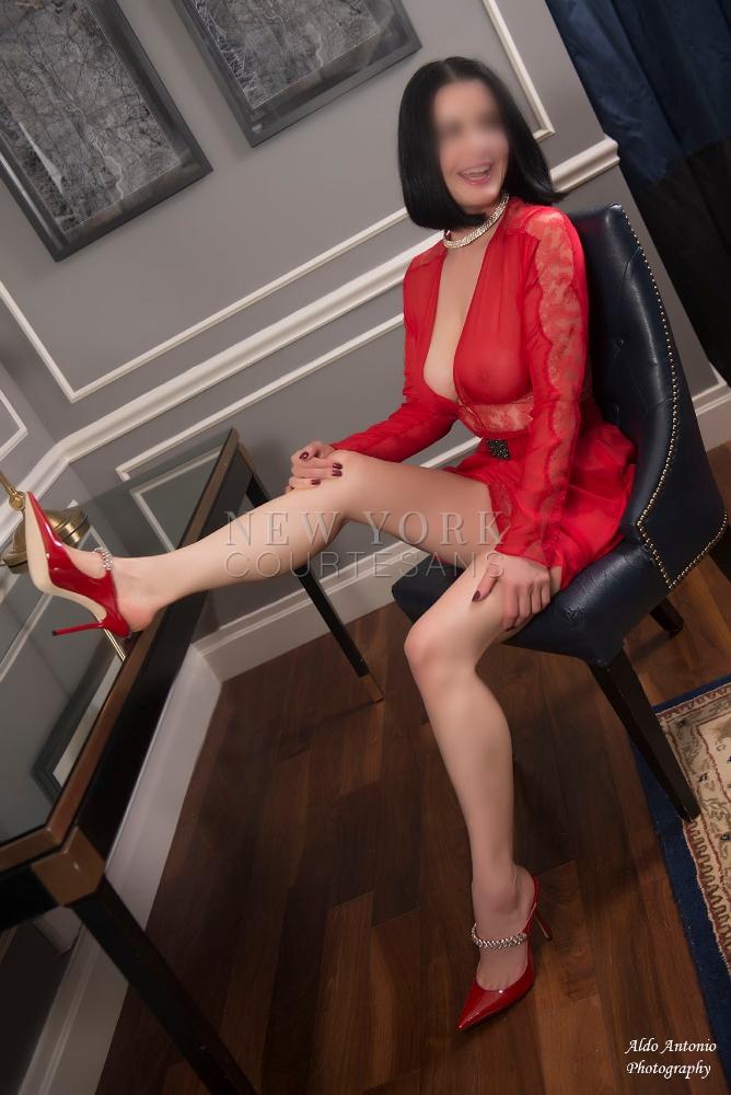 Elegant mature escort NYC Sara Charles in red see-through dress and high heels